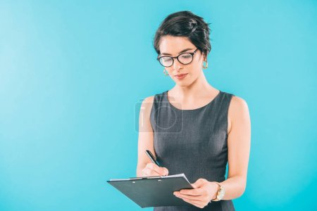 attentif mixte femme d'affaires en lunettes écriture dans le presse-papiers isolé sur bleu