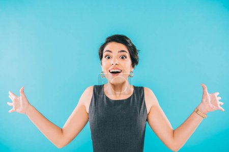 Photo for Excited mixed race woman gesturing while looking at camera isolated on blue - Royalty Free Image