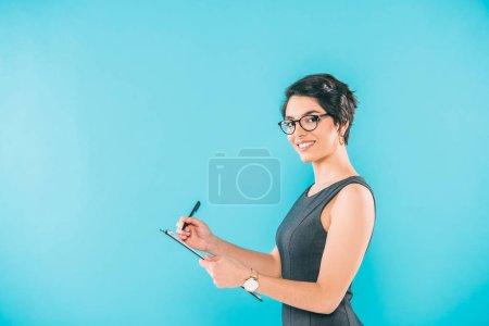 Photo pour Attrayant mixte femme d'affaires écriture sur presse-papiers tout en regardant la caméra isolée sur bleu - image libre de droit