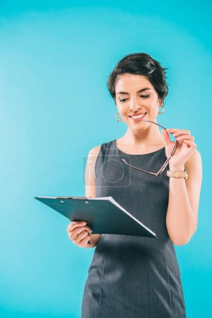 Photo for Cheerful mixed race businesswoman holding glasses while looking at clipboard isolated on blue - Royalty Free Image