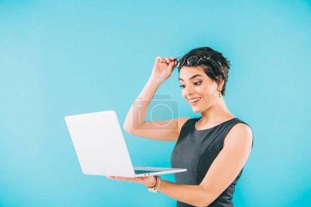 Photo pour Femme d'affaires mixte surprise de course touchant des glaces tout en utilisant l'ordinateur portatif isolé sur le bleu - image libre de droit