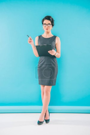 Photo for Attractive mixed race businesswoman holding clipboard and looking at camera on blue background - Royalty Free Image