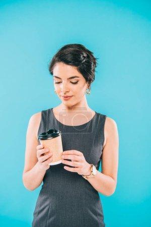 Photo pour Coûteux mixte femme tenant tasse en papier et regardant vers le bas isolé sur bleu - image libre de droit