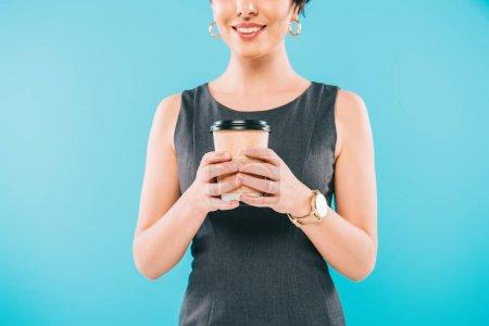 recortado disparo de sonriente mujer de raza mixta sosteniendo taza desechable aislado en azul