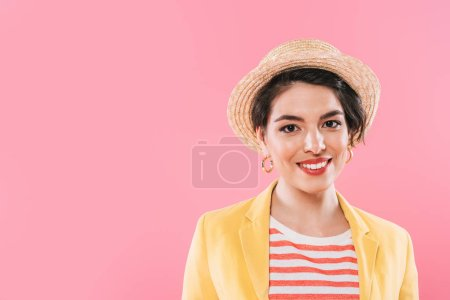 cheerful mixed race woman in straw head smiling at camera isolated on pink
