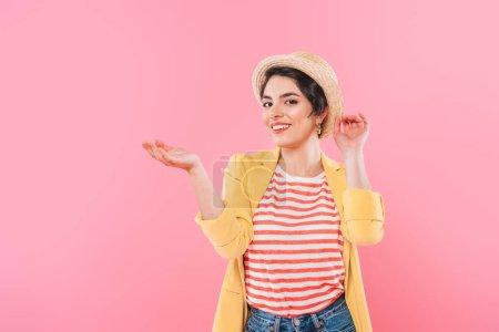 Photo pour Attrayant mixte race fille en paille chapeau posant à la caméra isolé sur rose - image libre de droit