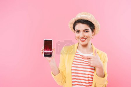 Photo for Cheerful mixed race woman pointing with finger at smartphone with trading courses app on screen isolated on pink - Royalty Free Image