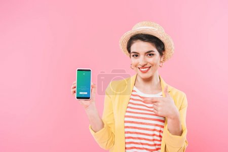Photo for KYIV, UKRAINE - APRIL 24, 2019: Pretty mixed race woman showing smartphone with Twitter app on screen isolated on pink. - Royalty Free Image