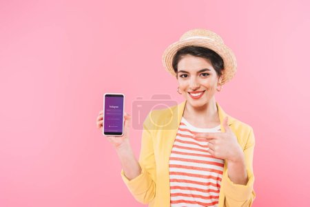 Photo for KYIV, UKRAINE - APRIL 24, 2019: Smiling mixed race woman showing smartphone with Instagram app on screen isolated on pink. - Royalty Free Image
