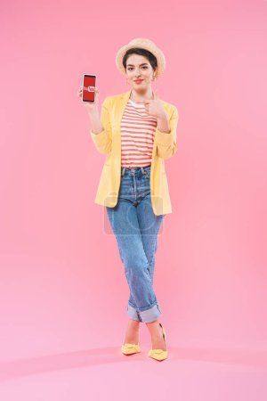 Photo for KYIV, UKRAINE - APRIL 24, 2019: Attractive mixed race woman showing smartphone with Youtube app on screen on pink background. - Royalty Free Image