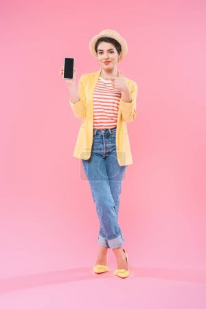 Photo for Smiling mixed race woman showing smartphone with blank screen on pink background - Royalty Free Image