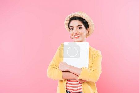 Photo pour Femme mélangée gaie de course retenant l'ordinateur portatif et souriant à l'appareil-photo d'isolement sur le rose - image libre de droit