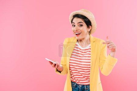 Photo pour Femme mélangéde de course de sourire pointant avec le doigt au smartphone d'isolement sur le rose - image libre de droit