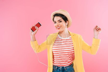 Photo for KYIV, UKRAINE - APRIL 24, 2019: Cheerful mixed race woman holding smartphone with Youtube app on screen and listening music in earphone isolated on pink. - Royalty Free Image