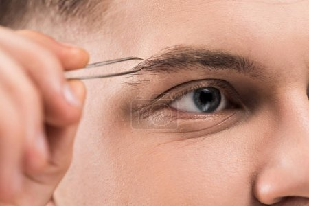 Photo for Close up view of young man using eyebrow tweezers - Royalty Free Image