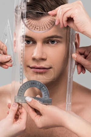 Photo for Cropped view of plastic surgeons measuring face with rulers and protractors isolated on grey - Royalty Free Image