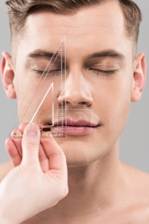 Photo for Cropped view of plastic surgeon measuring face with ruler isolated on grey - Royalty Free Image