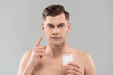 Photo for Front view of naked young man holding cosmetic container and applying face cream isolated on grey - Royalty Free Image