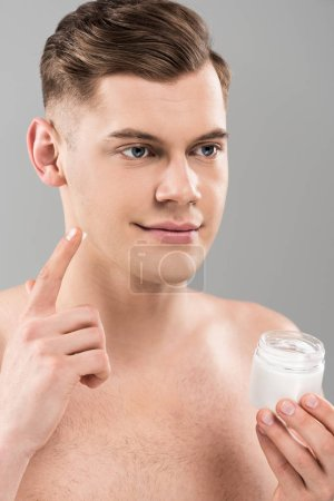 Photo for Naked young man holding cosmetic container and applying face cream isolated on grey - Royalty Free Image