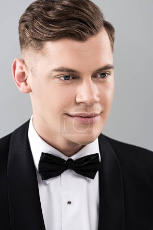 Photo for Smiling young man in formal wear with bow tie isolated on grey - Royalty Free Image