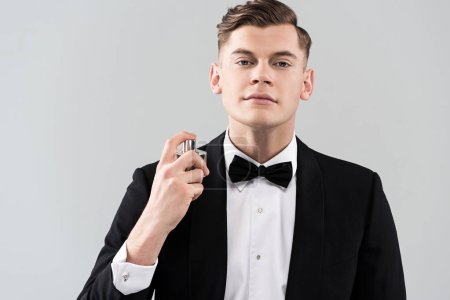 front view of confident man in formal wear applying perfume isolated on grey