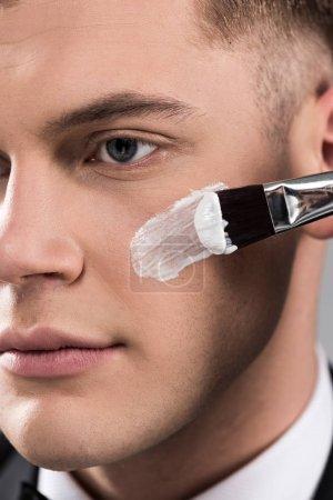 Photo pour Fermer vers le haut la vue de l'homme appliquant la crème sur le visage avec le pinceau cosmétique - image libre de droit