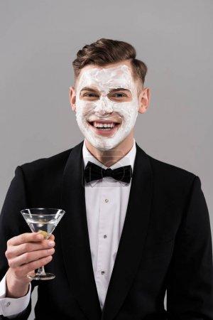 Photo pour Vu de devant d'un homme souriant en tenue officielle avec de la crème sur le visage tenant un verre de cocktail isolé sur gris - image libre de droit