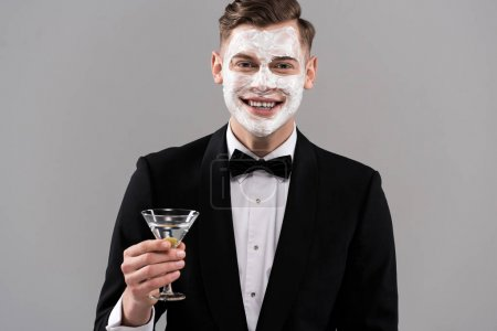 Photo pour Front view of smiling man in formal wear with cream on face holding glass of cocktail isolated on grey - image libre de droit