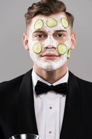 Photo for Young man in formal wear with cucumber facial mask isolated on grey - Royalty Free Image