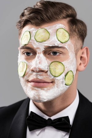 Photo pour Young man in formal wear with cucumber facial mask isolated on grey - image libre de droit