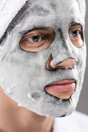 Photo pour Portrait de l'homme avec la serviette sur la tête et le masque facial mousseux regardant loin - image libre de droit