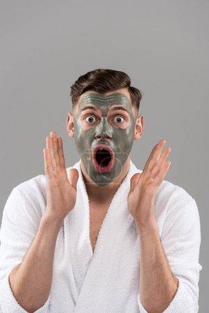 Photo pour Vue de devant d'un homme secoué en peignoir avec masque d'argile vue d'une caméra avec bouche ouverte isolée sur gris - image libre de droit