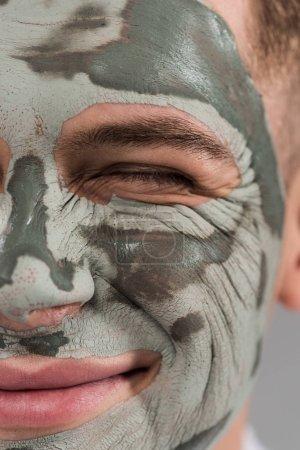 Photo pour Vue recadrée du jeune homme de sourire avec le masque d'argile avec l'oeil fermé - image libre de droit