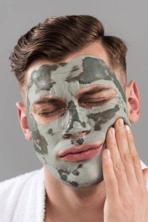 Photo pour Jeune homme mécontent avec le masque d'argile touchant le visage d'isolement sur le gris - image libre de droit