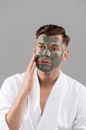 Photo pour Worried man with clay mask in white bathrobe touching face isolated on grey - image libre de droit