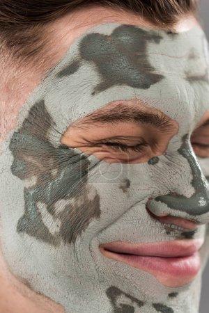 Photo pour Fermez-vous vers le haut de la vue du jeune homme de sourire avec le masque d'argile avec les yeux fermés - image libre de droit