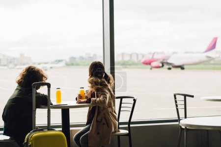 Photo for Two kids sitting in waiting hall and looking out window on plane - Royalty Free Image