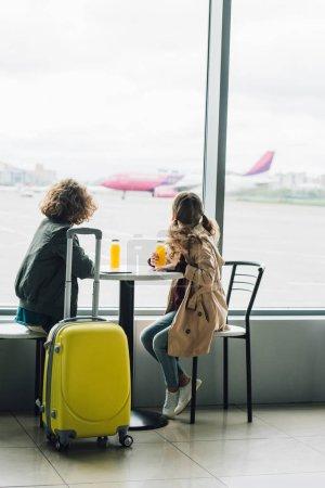 Photo pour Enfants s'asseyant à la table avec le jus près de la valise jaune et regardant par la fenêtre sur l'avion - image libre de droit