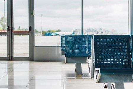 Photo pour Hall d'attente à l'aéroport avec sièges bleus et fenêtre - image libre de droit