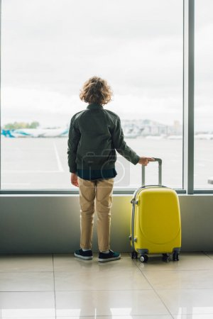Photo for Back view of boy standing near window, holding yellow suitcase - Royalty Free Image