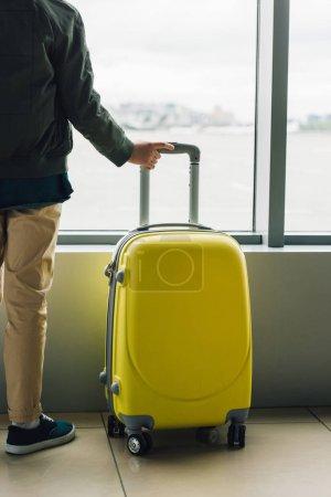 Photo pour Vue recadrée de garçon retenant la valise jaune, restant près de la fenêtre dans le hall d'attente - image libre de droit