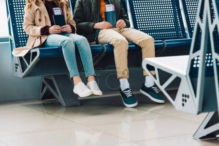 Photo pour Vue recadrée des enfants s'asseyant sur des chaises bleues et tenant des passeports dans le hall d'attente dans l'aéroport - image libre de droit