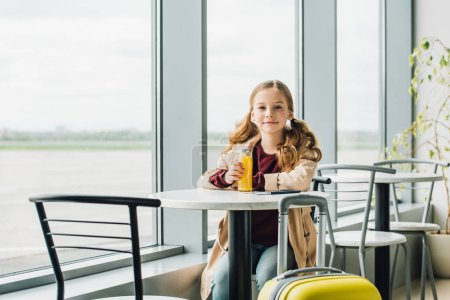 Photo for Preteen kid sitting in waiting hall in airport, drinking orange juice - Royalty Free Image