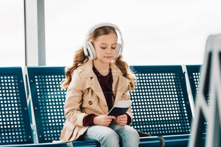 Photo for Preteen kid sitting on blue seat, holding passport and listening to music in waiting hall in airport - Royalty Free Image
