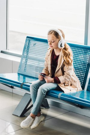 Photo for Full length view of preteen kid sitting on blue seat, holding passport and listening to music in waiting hall in airport - Royalty Free Image