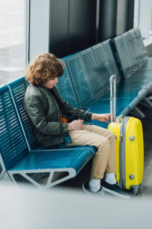 Photo for Side view of boy holding passport and sitting on blue seat near yellow suitcase in waiting hall in airport - Royalty Free Image