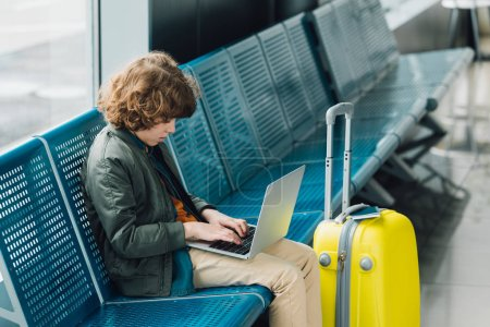 Photo for Side view of boy typing on laptop and sitting on blue seat near yellow suitcase in waiting hall in airport - Royalty Free Image