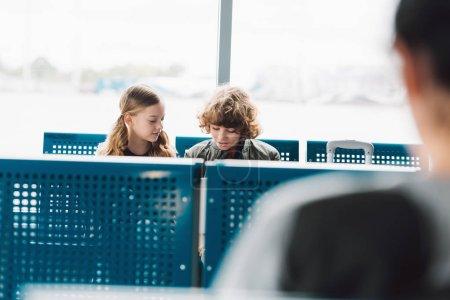 Photo pour Enfants assis et parlant dans le hall d'attente avec des sièges bleus à l'aéroport - image libre de droit