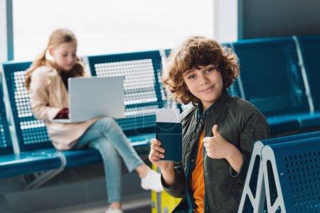 Foto de Enfoque selectivo en el niño sosteniendo el pasaporte y mostrando el pulgar hacia arriba mientras se sienta en el asiento azul en la sala de espera - Imagen libre de derechos