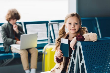 Photo for Selective focus on preteen kid holding passport and sitting on blue seat in waiting hall - Royalty Free Image